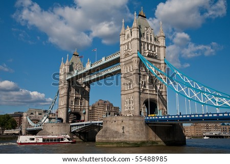 Tower Bridge in London with a boat full of tourists passing through