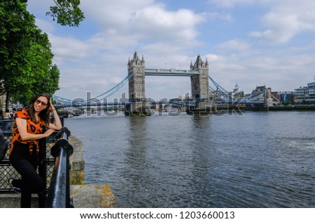 Tower Bridge, London, UK - June 8, 2018: Tower Bridge seen from the walkway and viewing point just before the Tower of London.  Shows a happy young lady posing for an iconic shot with Tower Bridge.