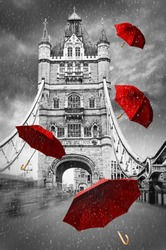 Tower Bridge on River Thames with flying umbrellas. London, England. Black and white concept graphic with red element.