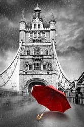 Tower Bridge on River Thames with umbrella on a raining day. London, England. Black and white concept graphic with red element.