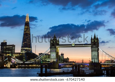 Tower Bridge, the Shard, city hall and business district in the background at night, London, Uk.