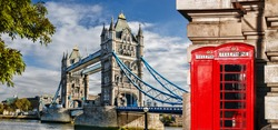 Tower Bridge with red phone booths in London, England, UK