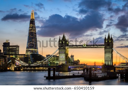 Tower Bridge with reflections at sunset in London, UK.