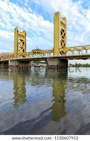 Tower Bridge with wispy sky reflected on the Sacramento River. Sacramento and Yolo Counties, California, USA. #1130607953