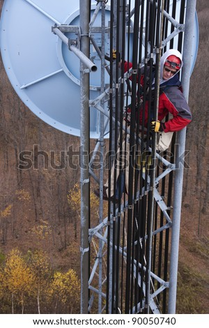 Tower climber inside the guyed tower measuring with the tape the elevation of the dish antenna