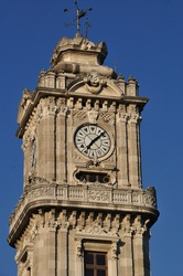 Tower clock. Close-up of an old stone tower with a round clock.