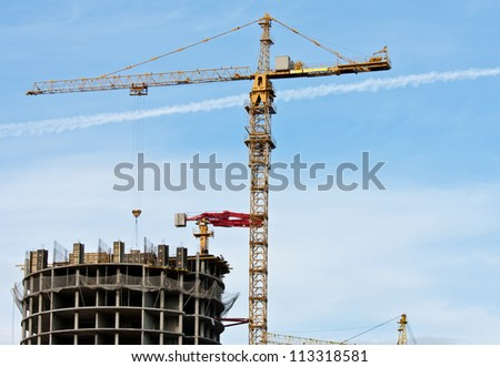 Tower crane and reinforced building under construction; project site against blue sky