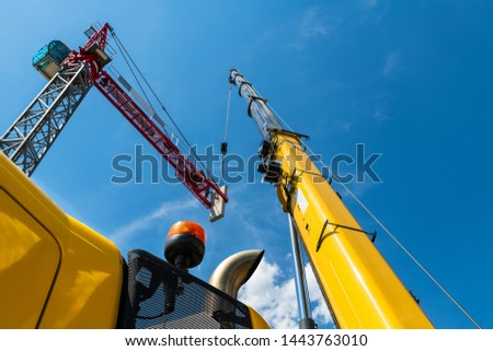 Tower crane assembly. Lifting device installation. Construction site. Placing a concrete counterweight by high telescopic boom of yellow mobile hoist machine. Blue sky. Bottom view. Building industry. #1443763010