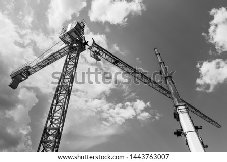 Tower crane installation. Black and white silhouette. Work at heights. Artistic construction background with sky and clouds. Telescopic boom of lifting device. Occupational safety. Building industry. #1443763007