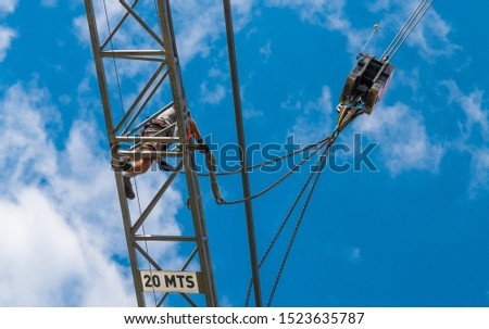 Tower crane installation. Working man on steel boom of building lifting machine. Hoist device detail on blue sky background. Bottom view of dangerous work at heights and belaying. Occupational safety. #1523635787