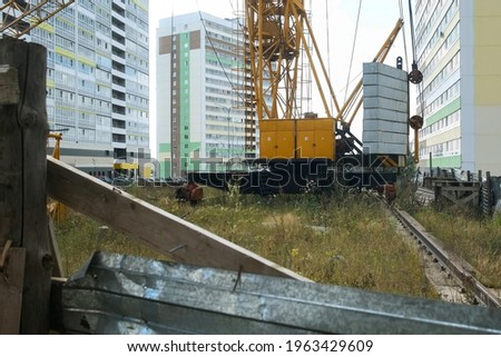 Tower crane on a construction site at high-rise building, closeup view. Construction of residential building in new city district. Cloudy warm day. Cheap panel houses in a third world country. stock photo