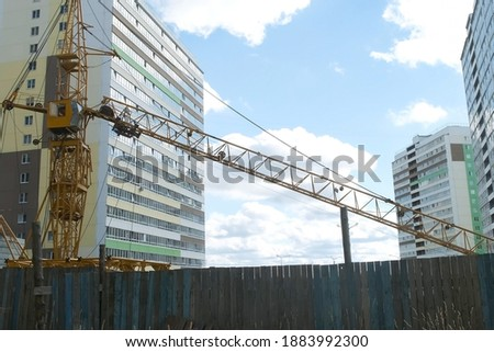 Tower crane on a construction site for lift a load at high-rise building. Construction of residential building in new city district. Cloudy warm day. Cheap panel houses in a third world country. stock photo