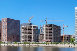 Tower cranes and residential apartment buildings under construction on river bank. Real estate development.