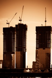 Tower cranes constructing a new residential buildings at a construction site. big building construction concept