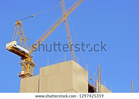 Tower cranes were on the top of building covered by safety protection border show how construction plan to organize position of tower cranes to make construction faster and importance of tower cranes.