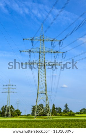 tower for electricity in rural landscape under blue sky