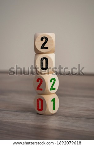 Tower made of cubes and dice with 2020 and 2021 on wooden background Stock photo ©
