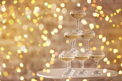 Tower made of glasses with champagne on table against blurred lights