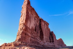 Tower of Babel Monument at The Arches National Park Moab Utah.  There is a man rock climbing on the cliff wall. The blue sky enhances the red rock and stone of this famous sandstone rock formation.