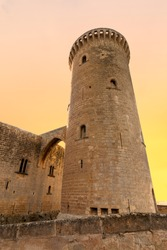 Tower of Bellver castle with orange sky in background in Mallorca, Spain. Historic building