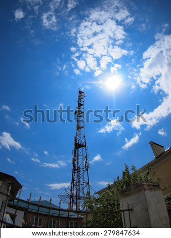 Tower of cellular communication against the blue sky and bright sun with wide angle fisheye lens and distortion view