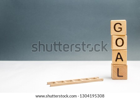 tower of cubes with an inscription goal and a fallen ladder. The concept of achieving the goal, subject to the application of all the efforts and desires. Tool for success. Don't give up half way.