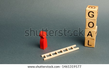 tower of cubes with an inscription goal and a red figure of a man stands near fallen ladder. concept of achieving the goal, subject to the application of all the efforts and desires. Tool for success.