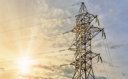 Tower of high voltage line on a background of blue cloudy sky and bright shining of sun