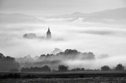 Tower of rural church in misty autumn morning.