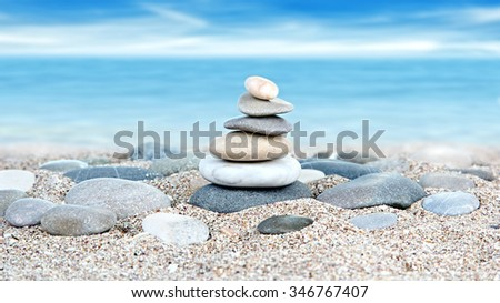 Tower of stones on sea beach background