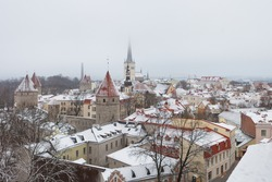 Tower of the city wall and Oleviste Catholic Church at the Old city of Tallinn in Estonia at the winter time. Gothic Scandinavian architecture of medieval charming city of Tallinn Old Town and snow.