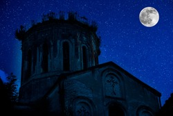 Tower of the Gothic church against a background of night sky with stars and full moon