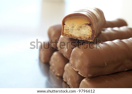 Tower of thin chocolate bars with one broken bar, caramel toffee spilling out