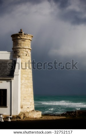 Tower on the shores of the Atlantic Ocean. South Africa. Dark sky (after the storm).