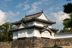 Tower Rokuban-yagura Turret, part of Osaka Castle structure, built on castle's wall, with traditional white walls and carved wooden roof.