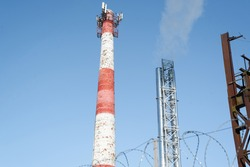 Tower with a pipe. Rising smoke into the clear light blue sky. Environmental pollution concept.