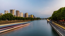 Towers and skyscrapers in Paris, France, used as office buildings as well as office buildings, by the water in front of barges on the river Seine in Quai de Grenelle, Front-de-Seine District. Paris