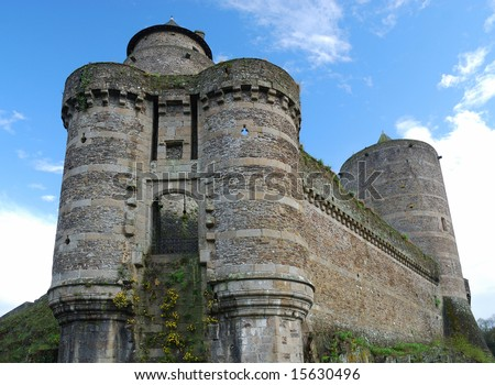 Towers of ruinous suspension bridge and surrounding wall against blue sky, castle  Fougeres, France