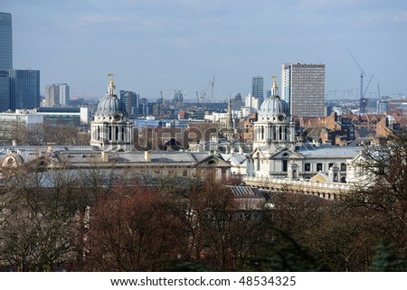 Towers of the Old Royal Naval College, Greenwich, London, UK, a world heritage site, with the construction of the 2012 Olympic Stadium in the background