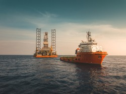 Towing vessel assisting drilling rig in positioning