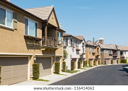 Town homes line up along the road in a new residential neighborhood.