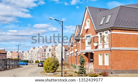 town house architecture on street of city panorama view against blue cloud sky landscape background modern residential building and road urban landmark in european russia at spring time #1352439077