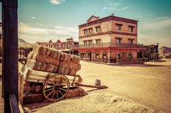 Town square as a western movie set. Spaghetti western. Cart loaded with straw bales. Travel concept