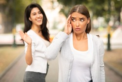Toxic People. Girl Avoiding Meeting Tiresome Female Friend Pretending Not Noticing And Ignoring Greeting Walking Outdoors. Selective Focus