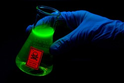 Toxic sample hold by a scientist in a laboratory - radioactive - fluorescence