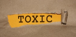 Toxic word uner Brown torn paper with yellow background. Addictions, quit smoking and drinking, bad habits and toxic relationship concept.
