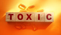 Toxic Word written on wooden cubes with Omega-3 pills around. Detoxication healthcare concept.