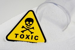 toxicity sign in white, sprinkled chemical powder with a measuring cup indicating the danger of a substance