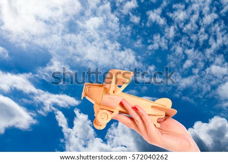 Toy airplane in hand - a symbol of travel and dreams - Shutterstock ID 572040262