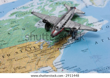 Toy Airplane on Map of North America.  Shallow depth of field from use of macro lens - stock photo